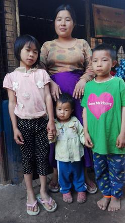 Mother and three children in front of their house