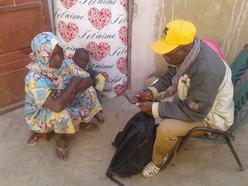 a man looking at his mobile phone sitting with a young woman and a child.