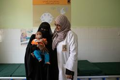 A female doctor stands beside a woman and her baby