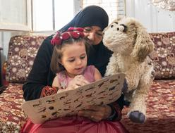 A young girl reading a book with her grandmother and a puppet