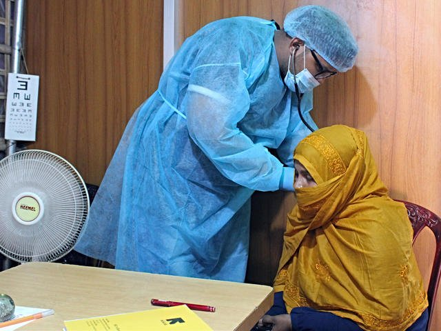 Dr. Sayed Muhaiminur Rahman examines Sakera at the IRC primary health care centre. He confirmed that she and her sons did not have COVID-19.