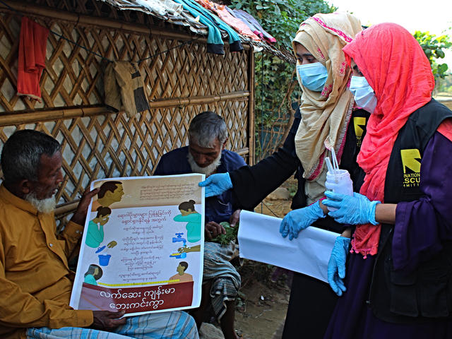 Umme Habiba, Rumana Afroz (wearing masks) and other IRC community health volunteers are trying to reach as many people as they can with information about how they can protect themselves from COVID-19.