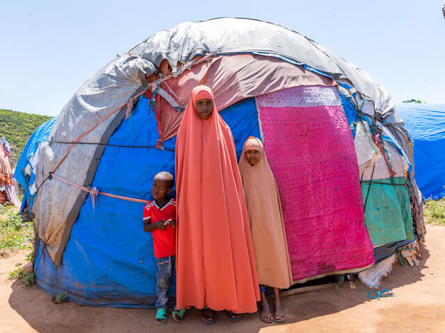 Misra standing in front of her tent with her children