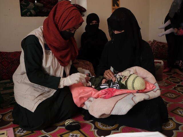 Dr. Bushra attending to a client and her baby during a field visit