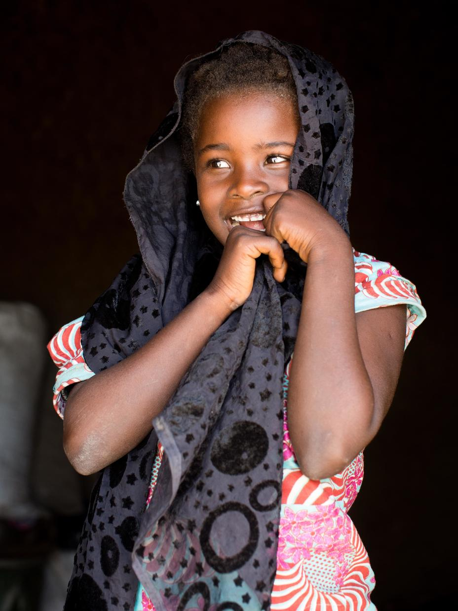 A young girl with headscarf is smiling