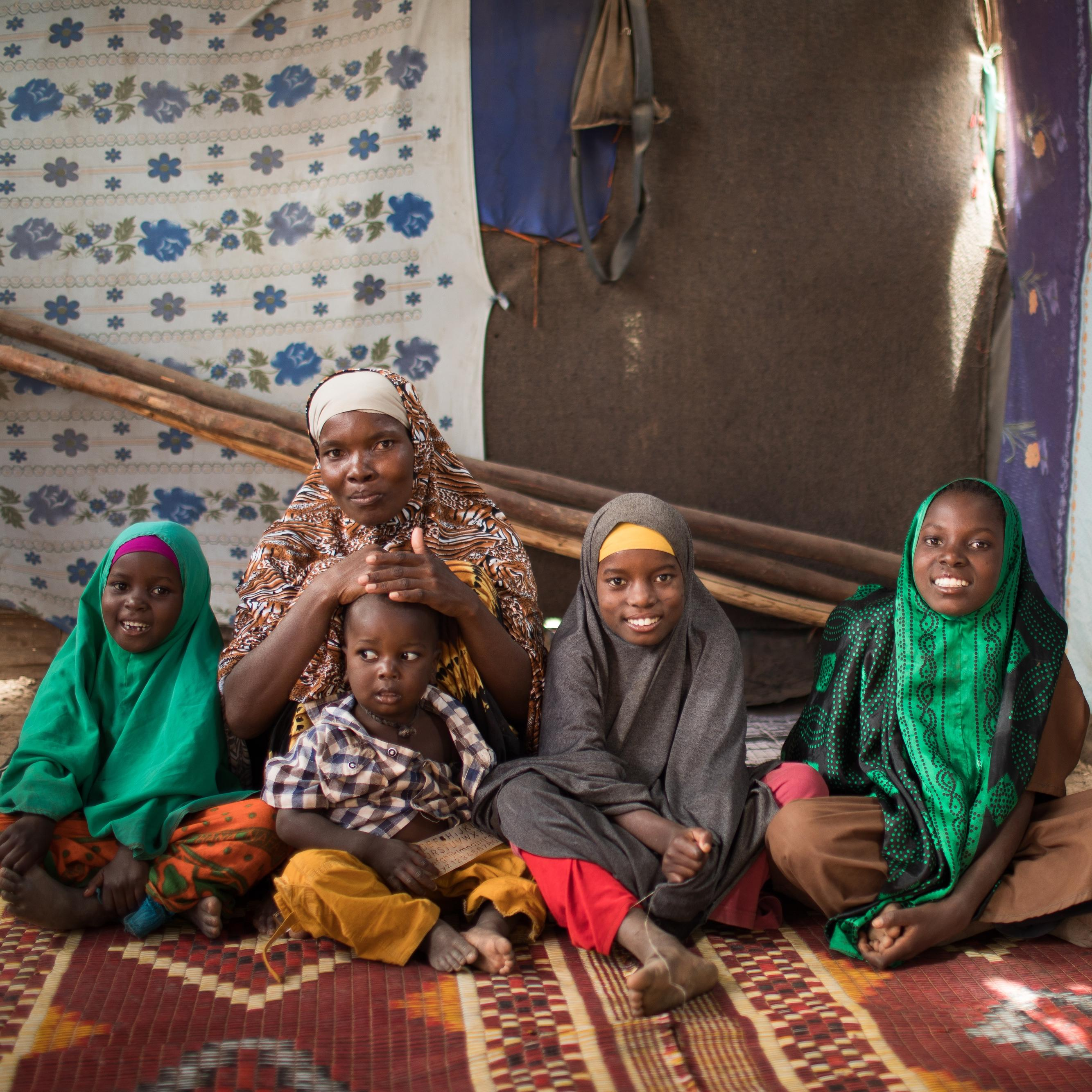 A mother with her four children sitting on a carpet