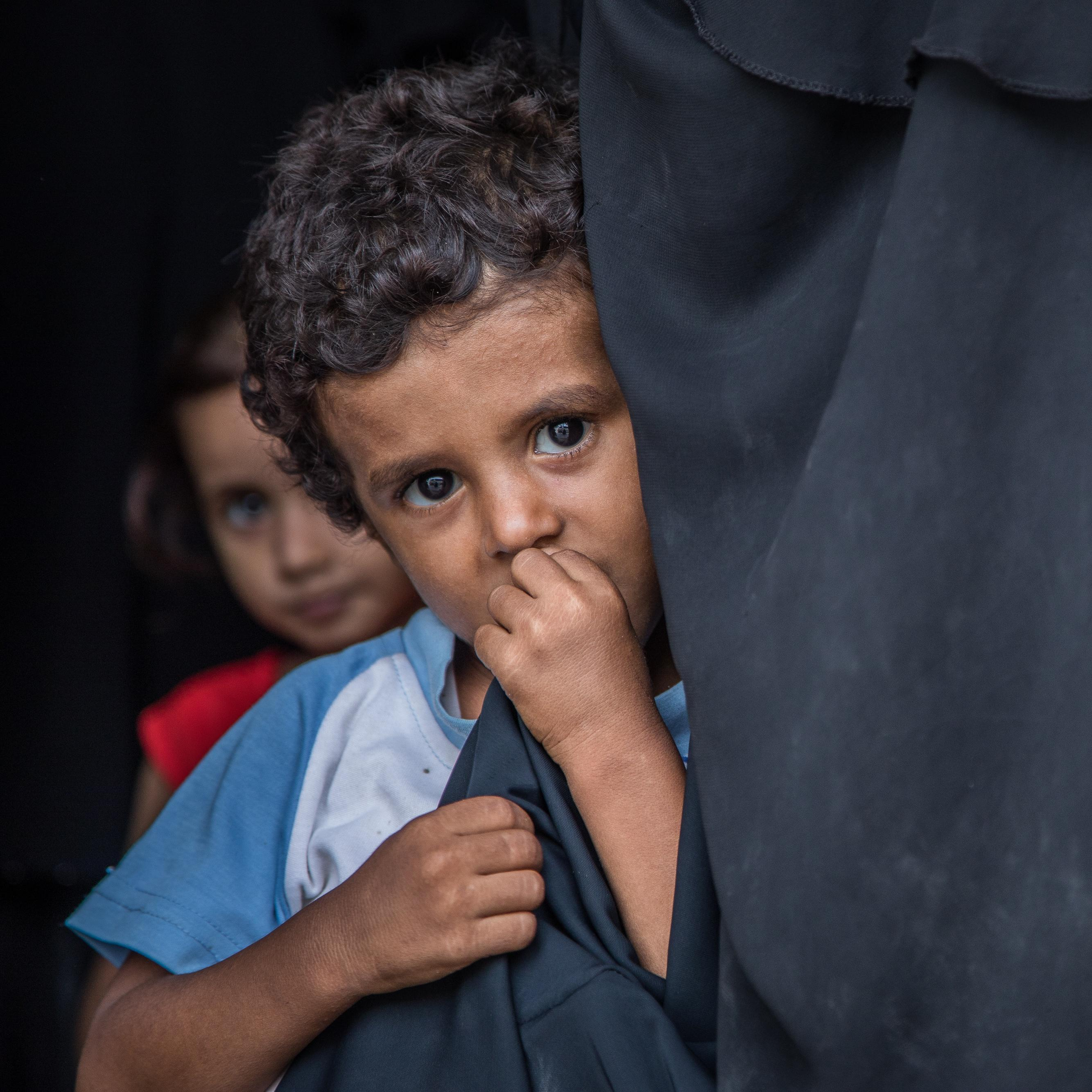 A young boy hiding behind a curtain