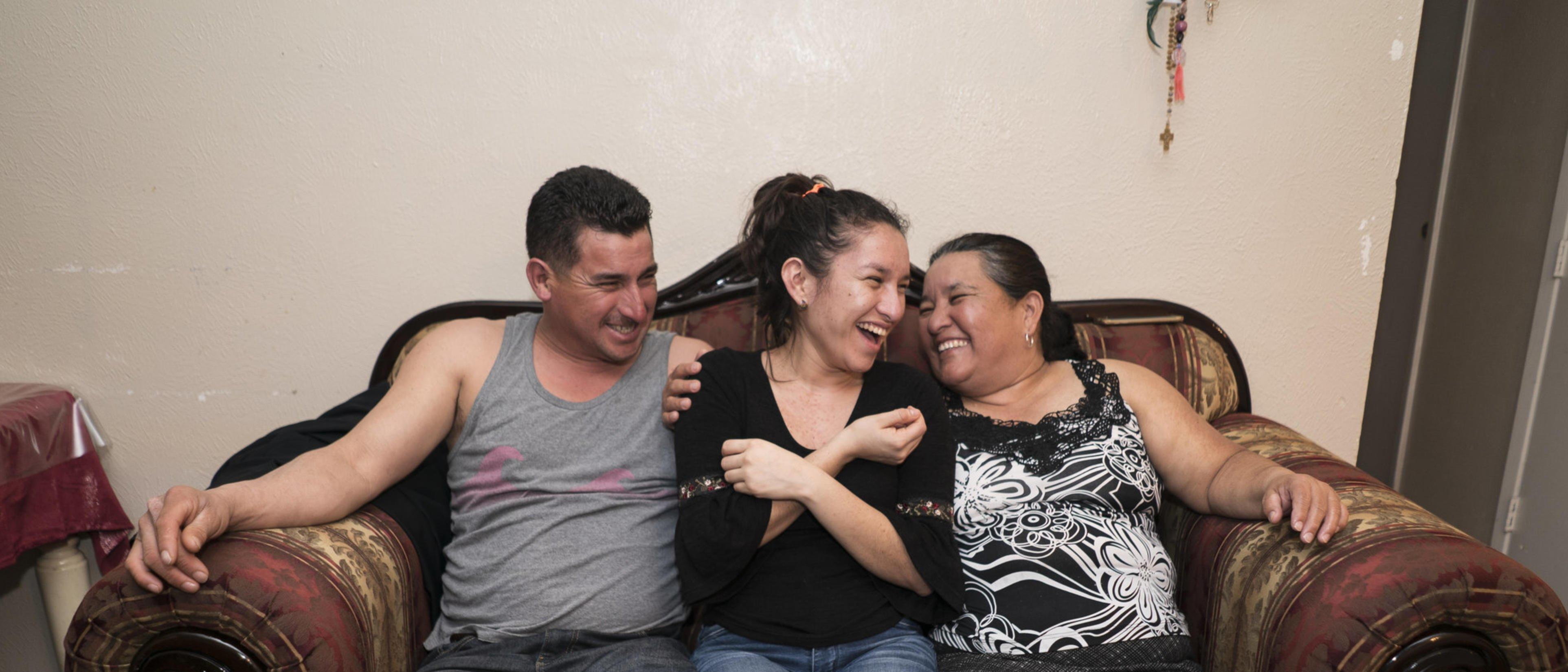 three laughing people sitting on a sofa