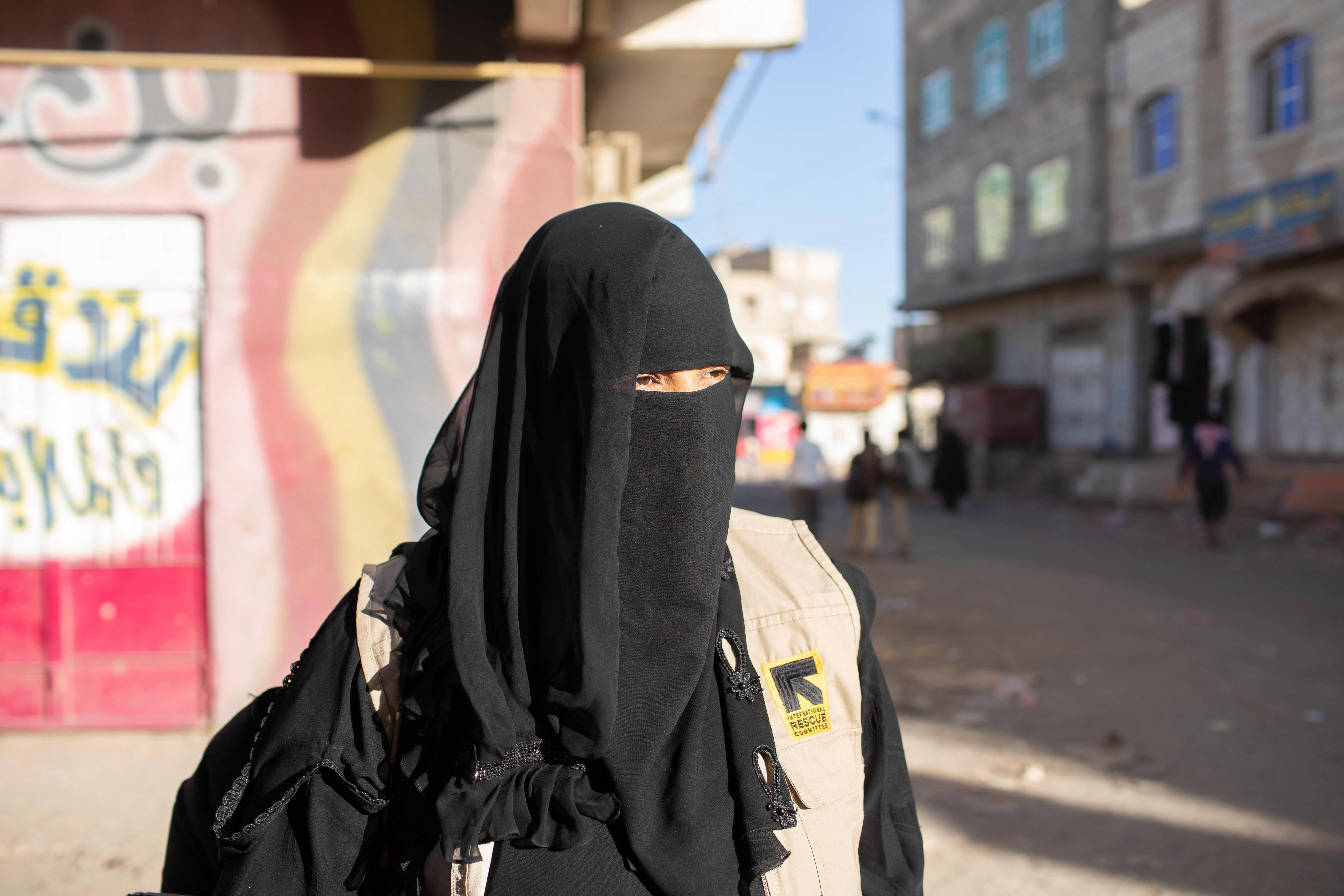 Tahani is fully veiled and is walking in a street