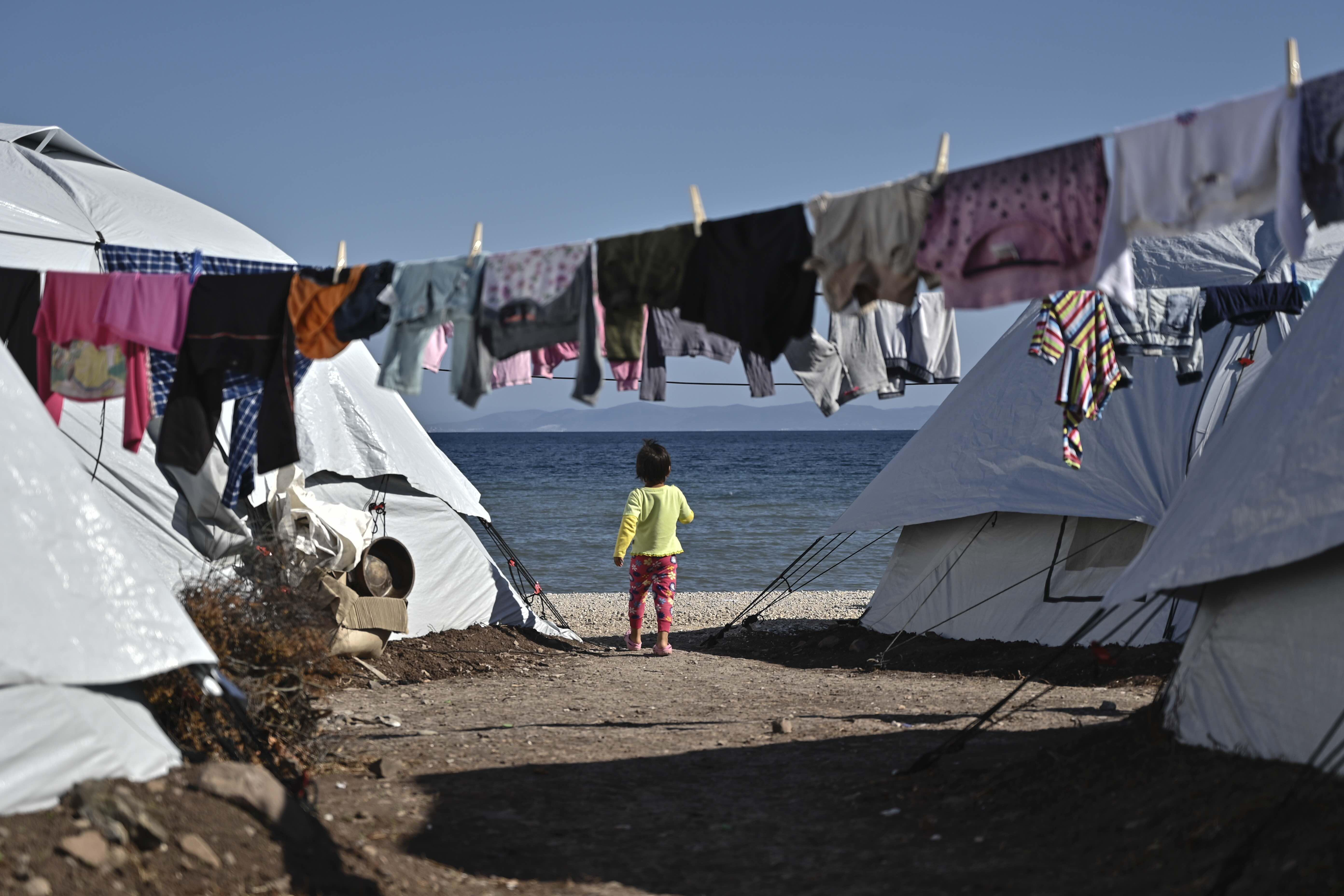 Child stands between tents at the new Lesvos camp