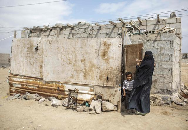A woman stands in front of a house together with her little son