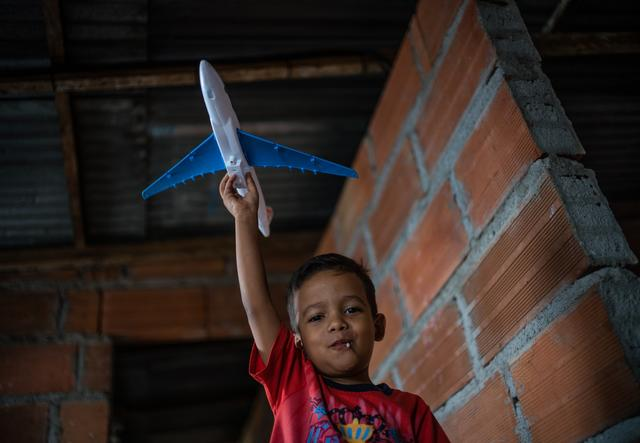 A young boy holding a toy plane in his hands