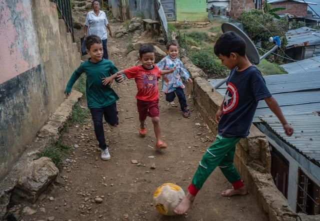 kids playing football in a narrow street