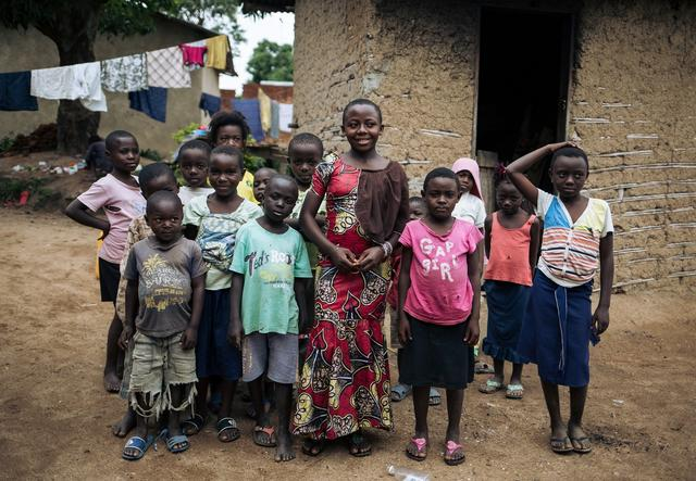 Christelle Muvingulwa in front of a group of children