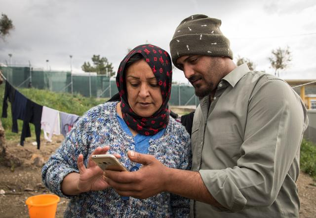 A man and a woman looking in a smartphone