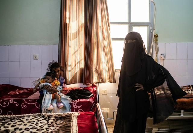 a little girl and a baby sit on a bed in a clinic - a fully veiled woman stands beside them