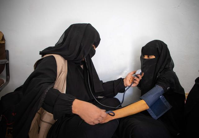 two fully veiled women, one taking the blood pressure of the other