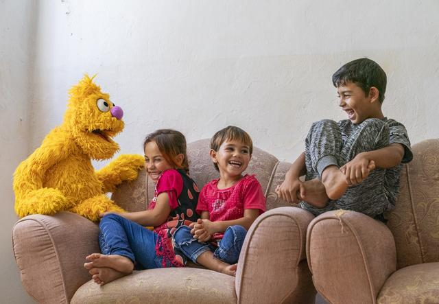 Sesame puppets with children on a couch