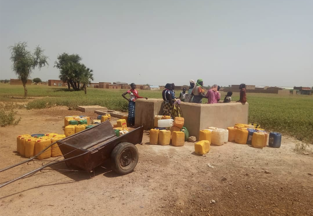 Some people stand around a well to fill fresh water in their jerrycans