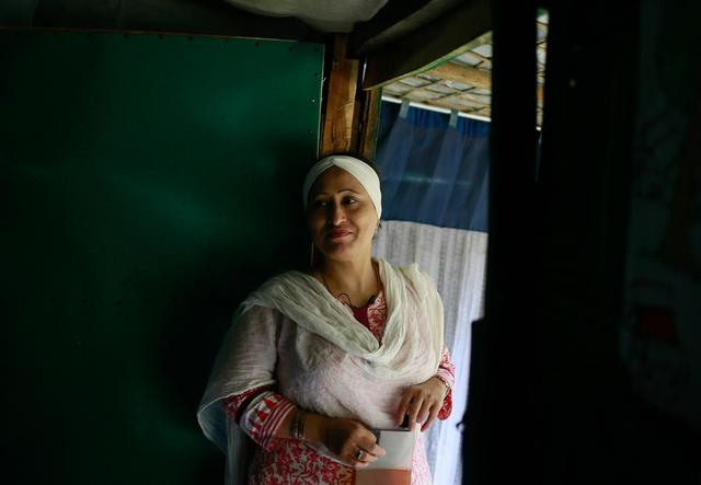Razia looks on at Rohingya women inside her women's centre, which she set up to help fight violence and discrimination against women in the camp.