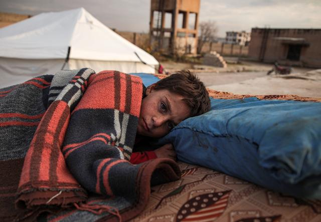 A Syrian child sleeps in the open at a displacement camp near Turkey's border after fleeing from southern Idlib.