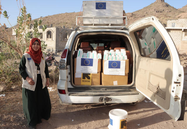 Dr. Bushra stands near an IRC mobile health van during a field visit