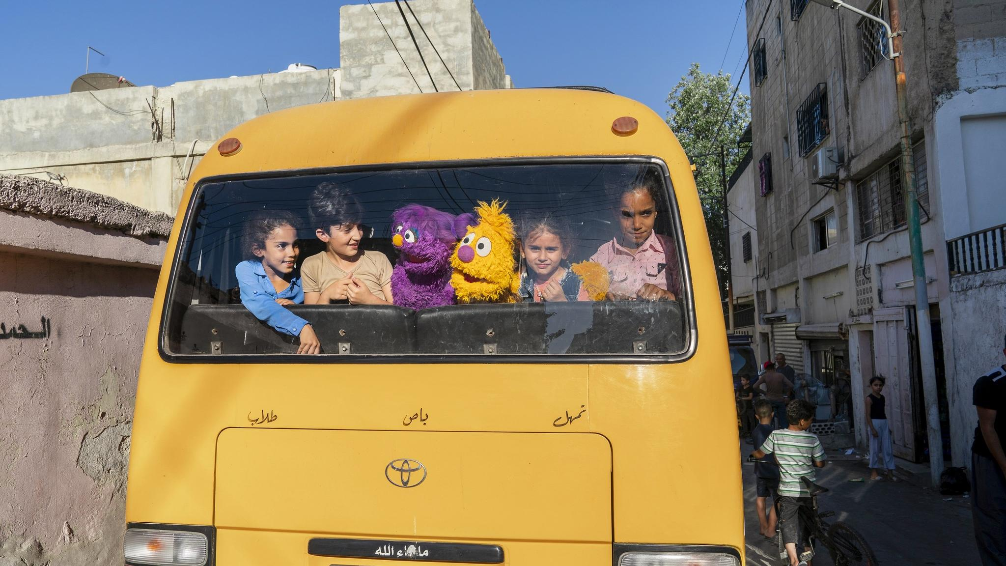 Kids and sesame street puppets looking out of the back window of a bus