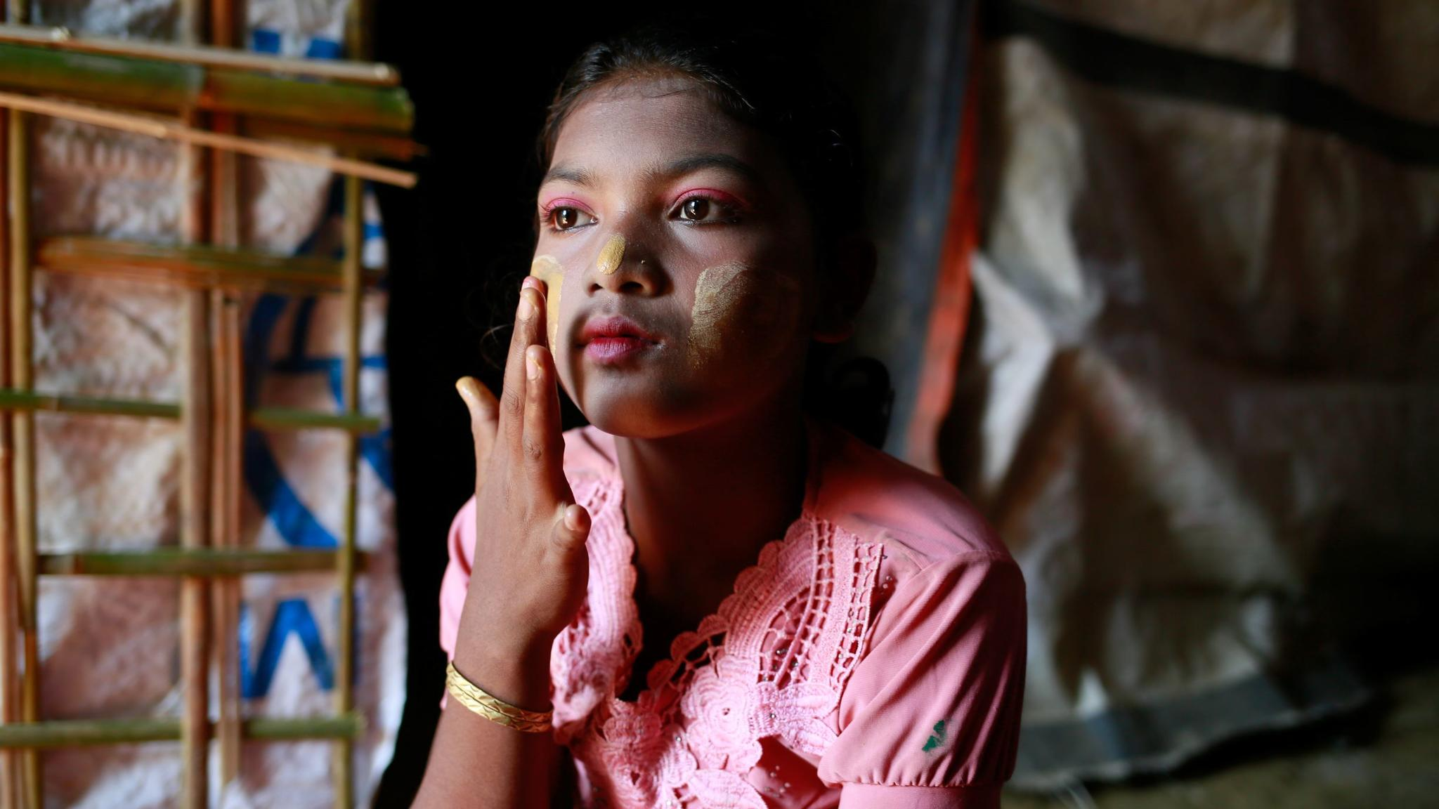Hasina, applying traditional make-up to her face