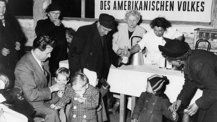 "food distribution to families. In the background a poster saying ""Spende des amerikanischen Volkes""."