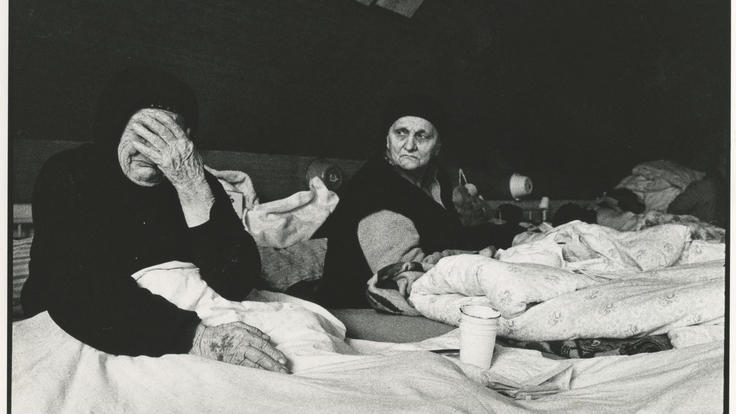 two elderly refugee women lying on matresses in a tent