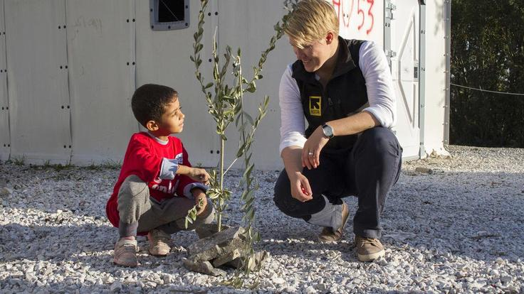 A young boy and IRC worker crouching besides a baby tree